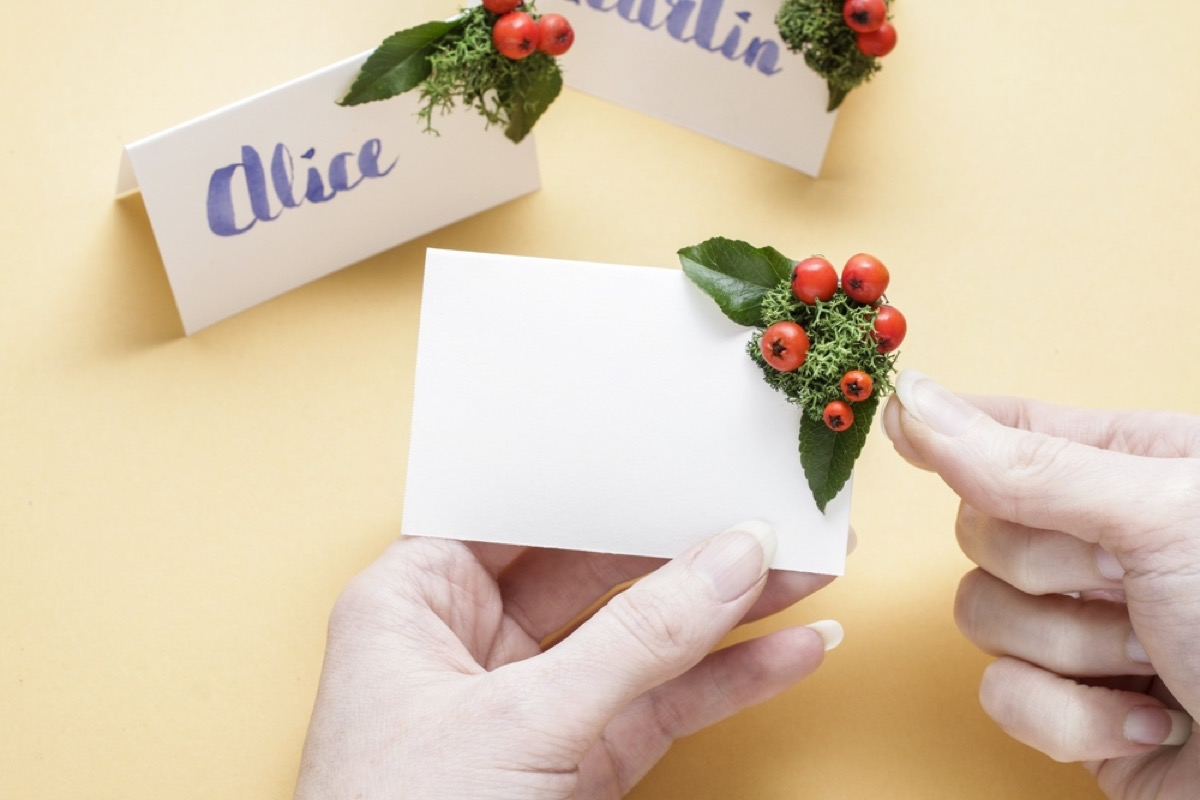 woman holding white place card and attaching holly berries in corner
