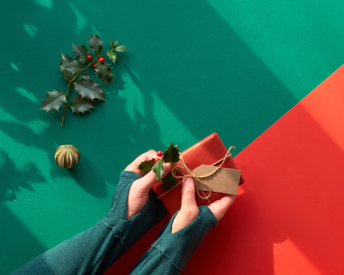 woman wrapping present in brown paper and attaching holly leaves and berries