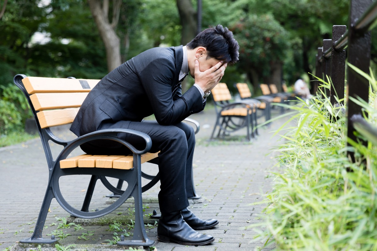 asian man in a suit sitting on a bench with his head in his hands