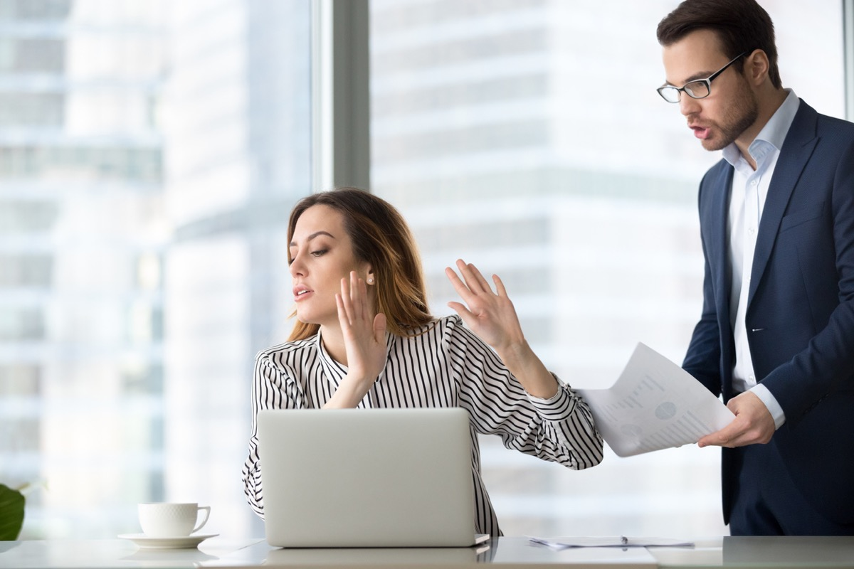 annoyed white woman at work rejecting a document from her male coworker
