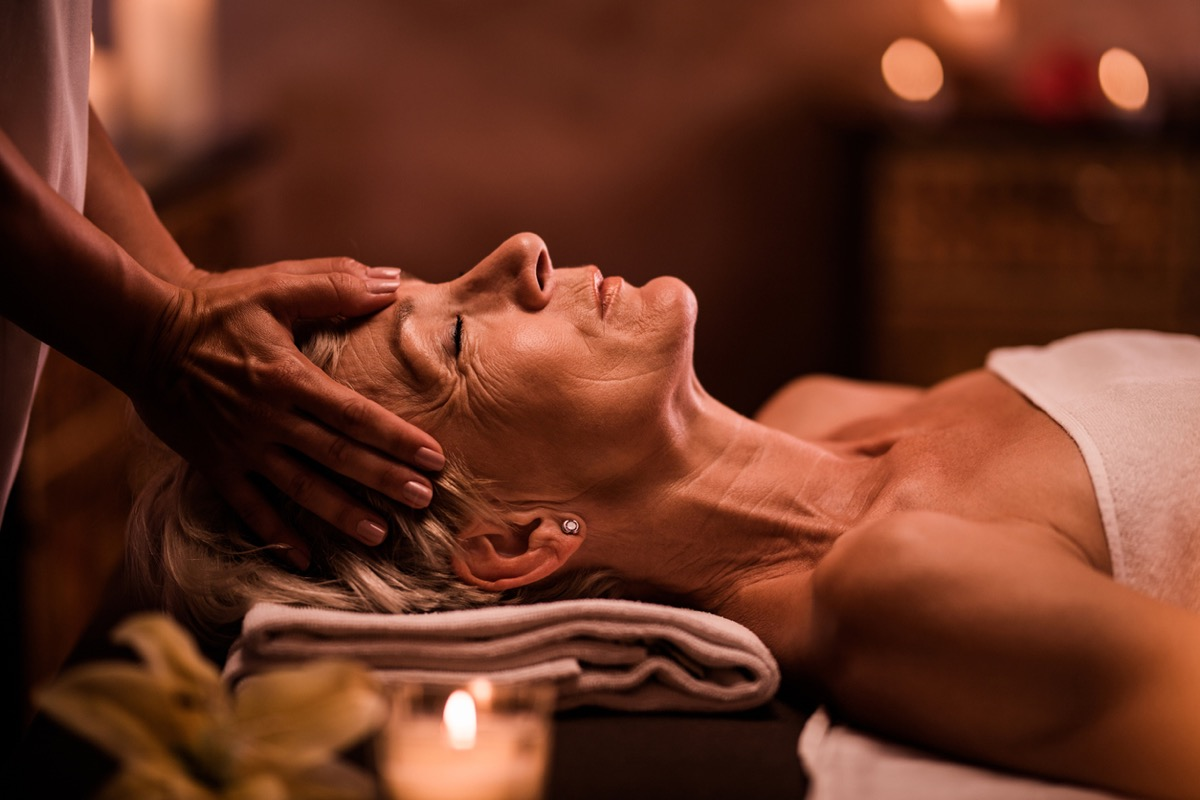 older white woman getting her head massaged at a spa