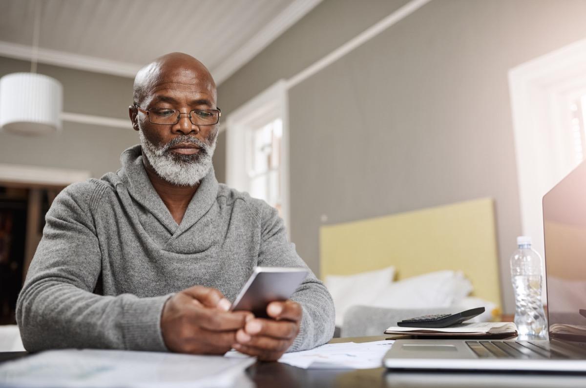 older black man checking his phone at his desk