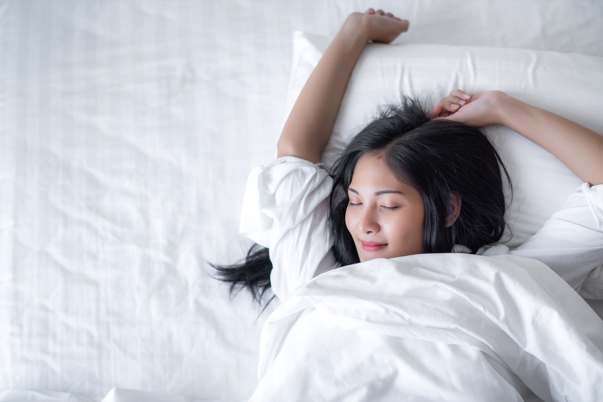 young asian woman waking up with a smile