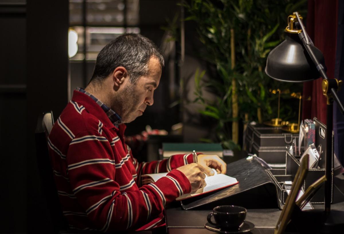older white man writing in notebook at night