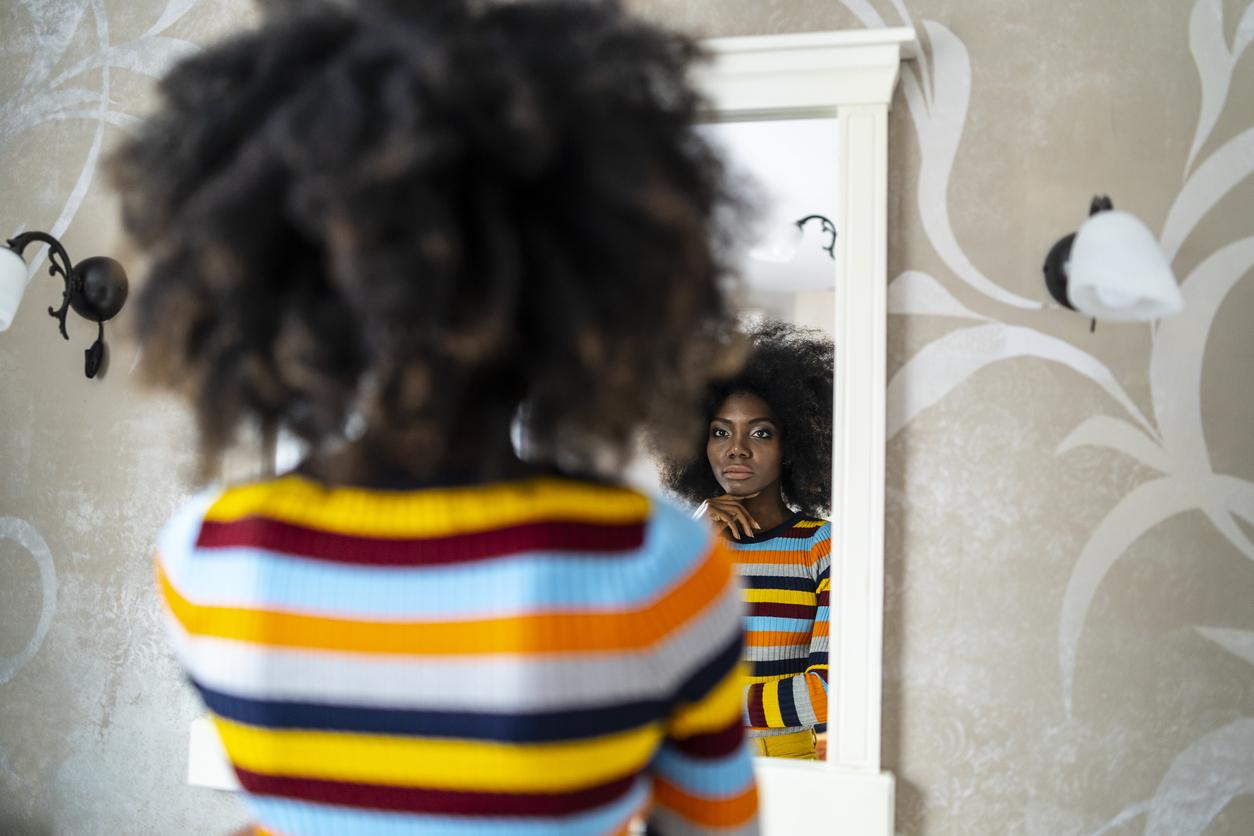 black woman looking in mirror