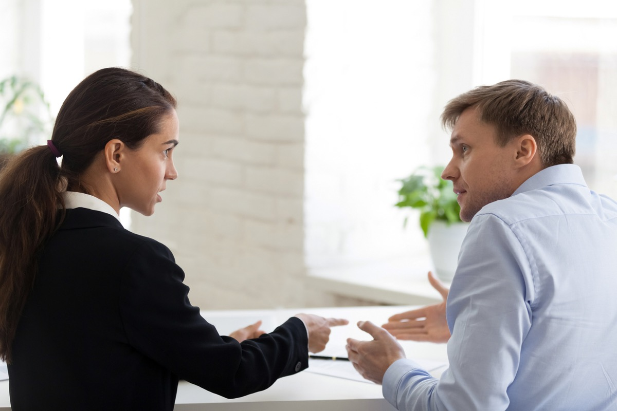 white woman at work pointing a finger at shrugging white male coworker
