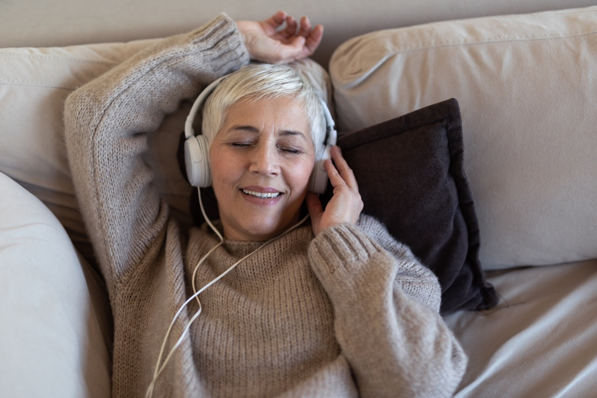 older white woman listening to music in bed