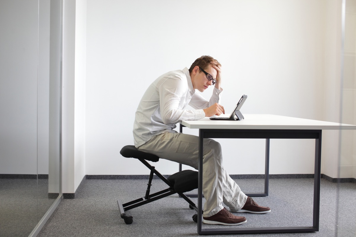 white man with bad posture slouching over his computer