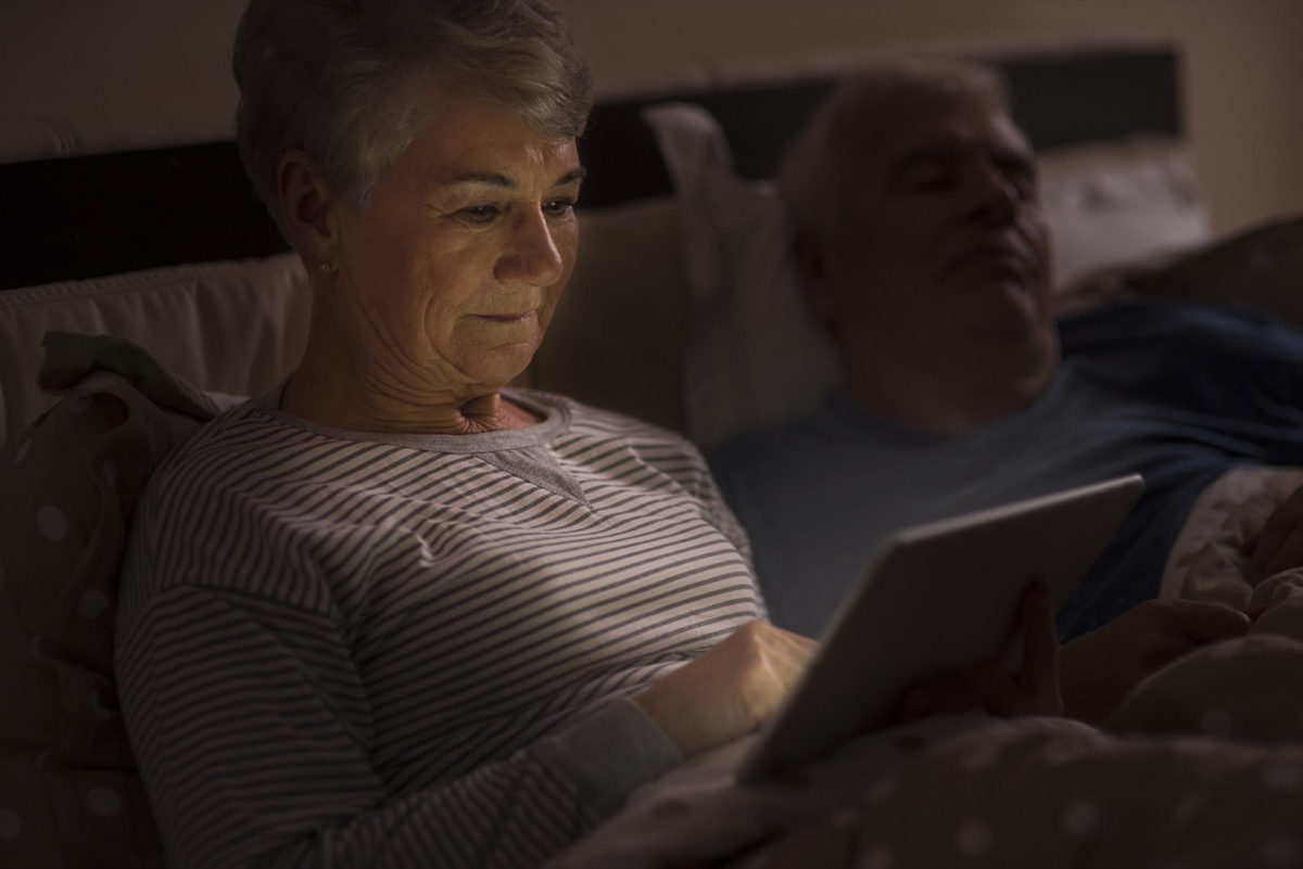 older white woman using ipad in bed while husband sleeps next to her