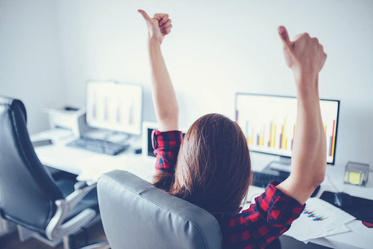 woman sitting at her computer giving two thumbs up