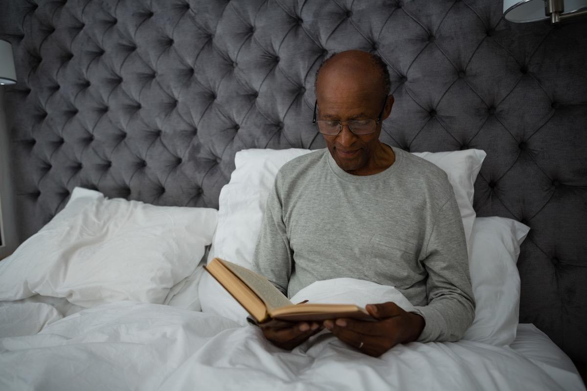 older black man reading a book in bed