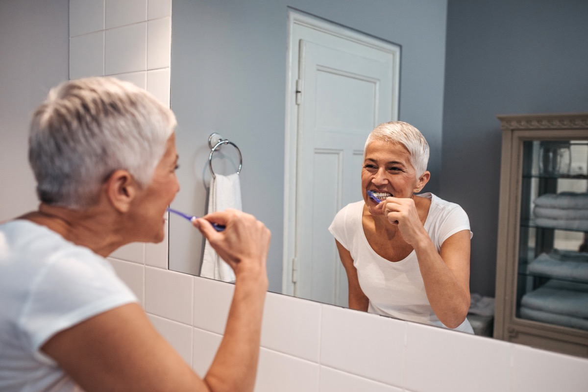 older white woman brushing her teeth in the mirror