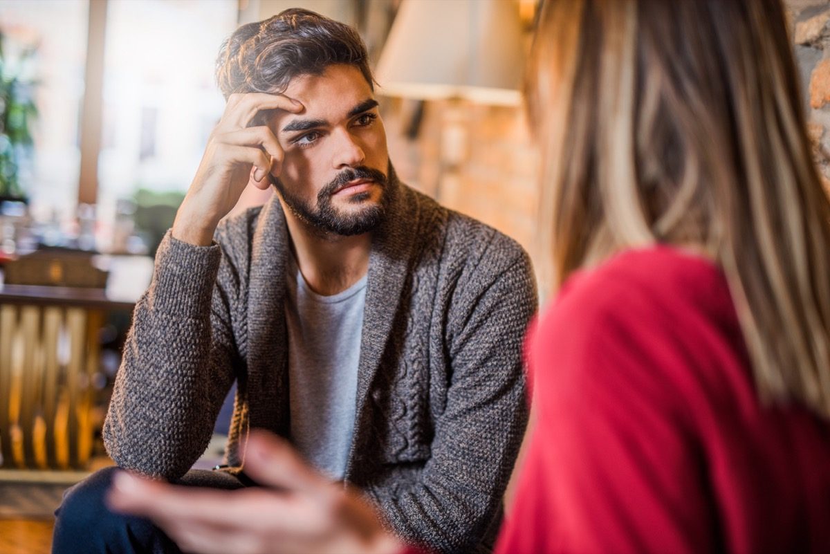 man looking annoyed while listening to woman complain