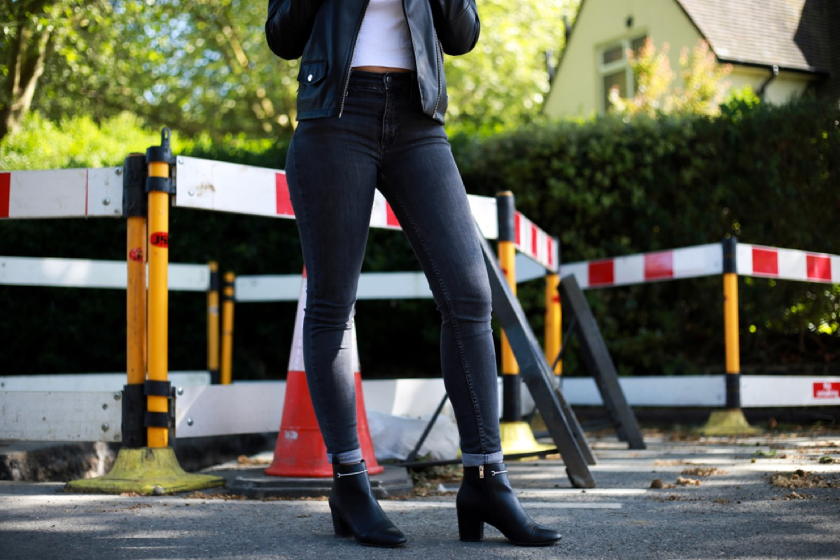 woman stands on street in jeggings, can only see her lower half