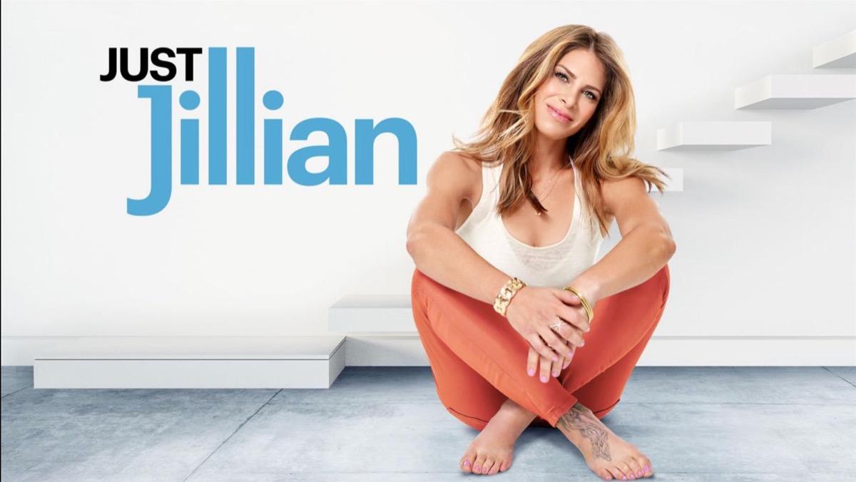 jillian michaels sitting cross-legged in orange yoga pants and white tank top