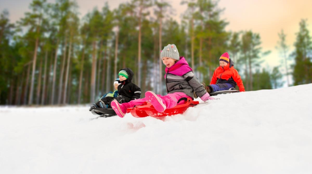 white children sledding in the snow