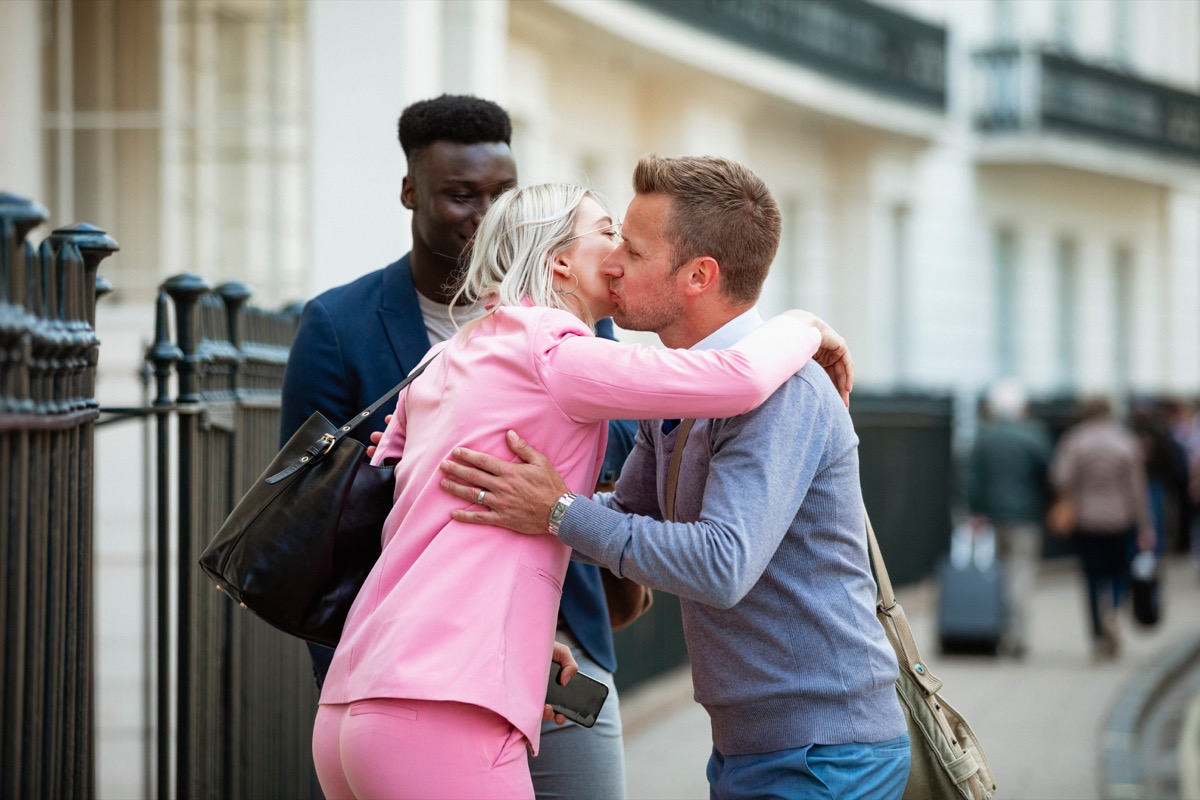 Man and woman greeting each other on the street with a kiss on the cheek