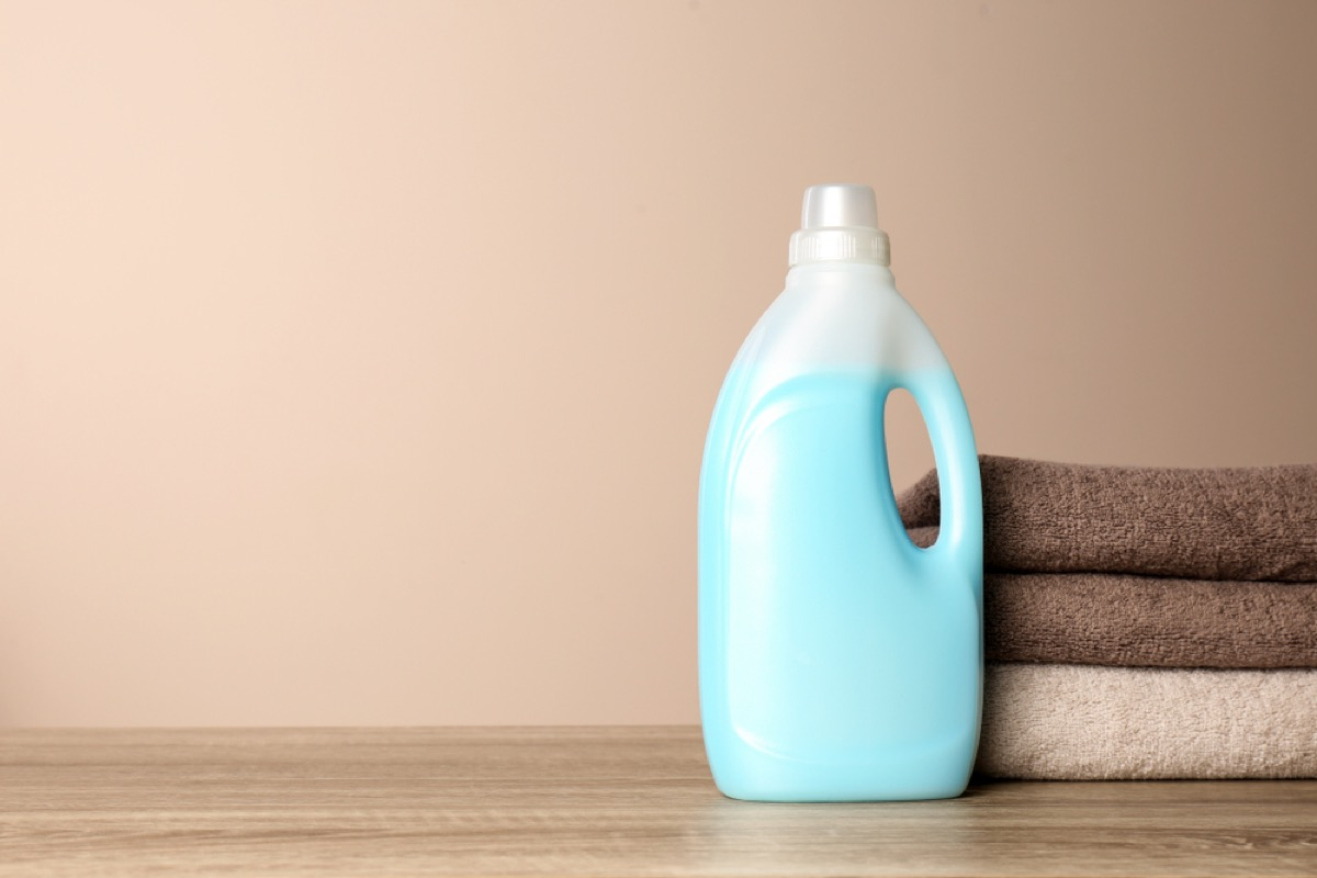 bottle of laundry detergent and stack of towels