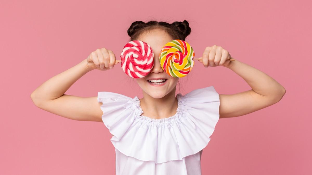 little girl holding two lollipops