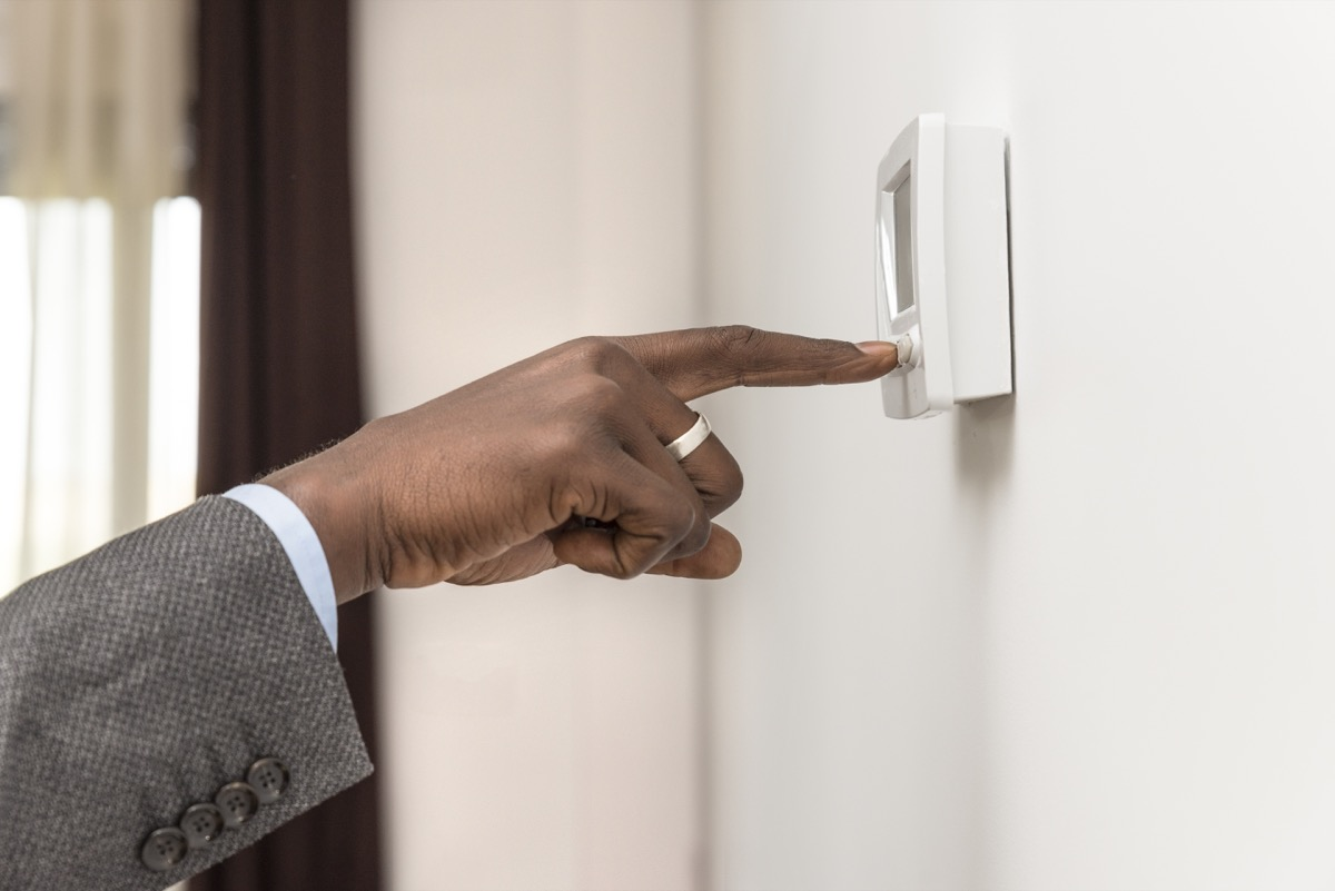 Man adjusting the temperature on a thermostat