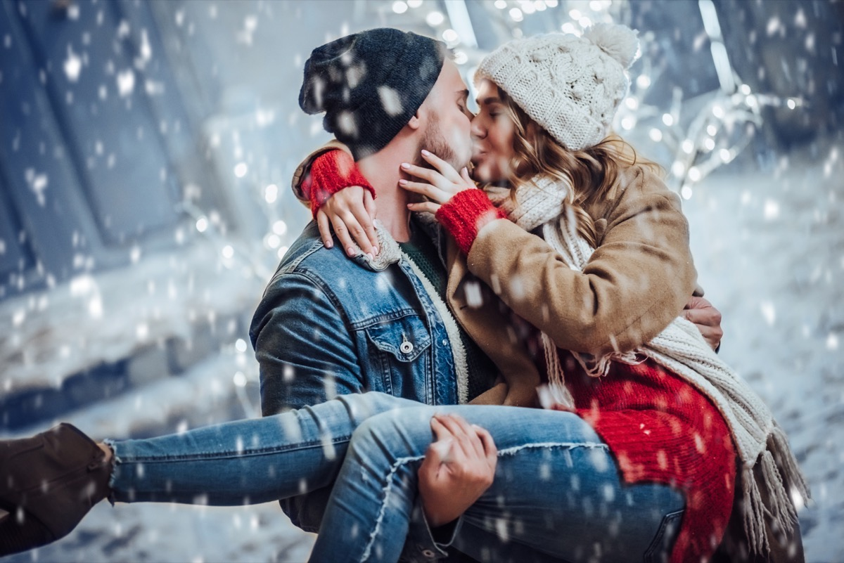 man and woman kissing in winter