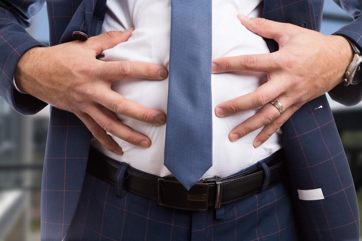 Man in a suit holding his bloated stomach