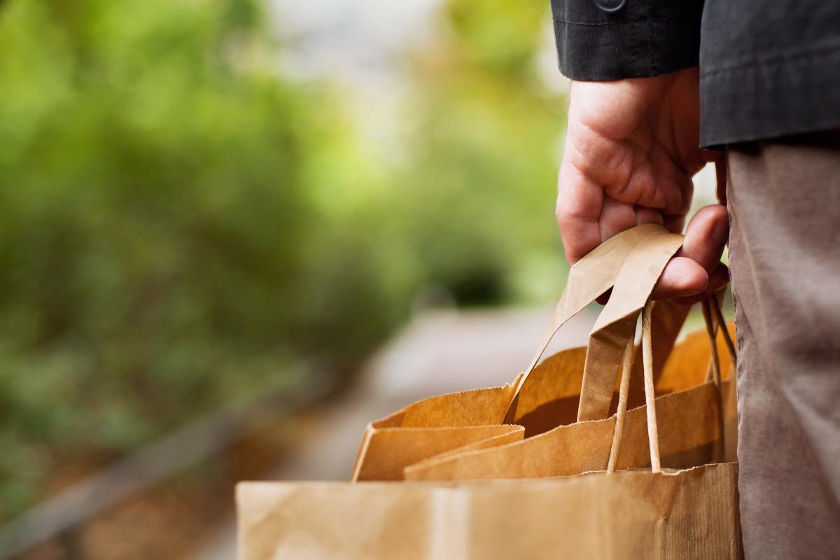 man carrying paper shopping bags