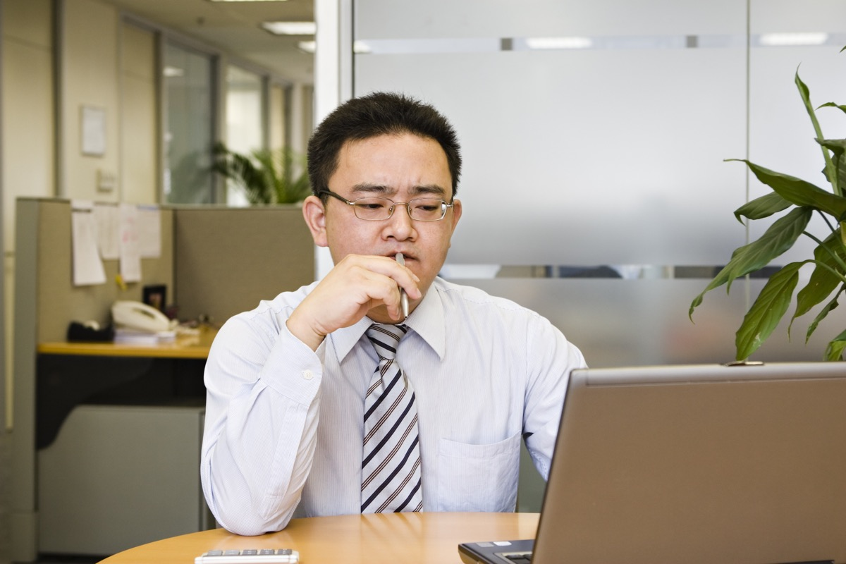 man chewing on a pen