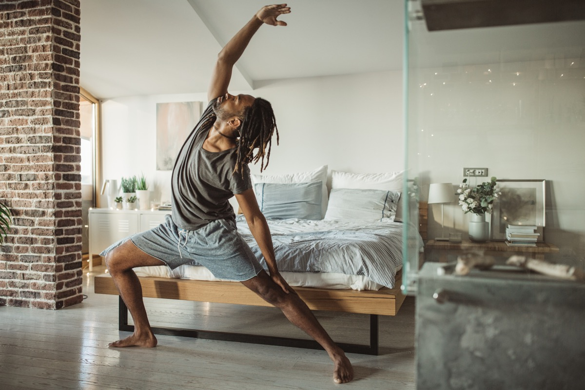 man doing yoga in his home