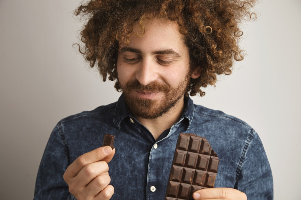Man eating squares of chocolate