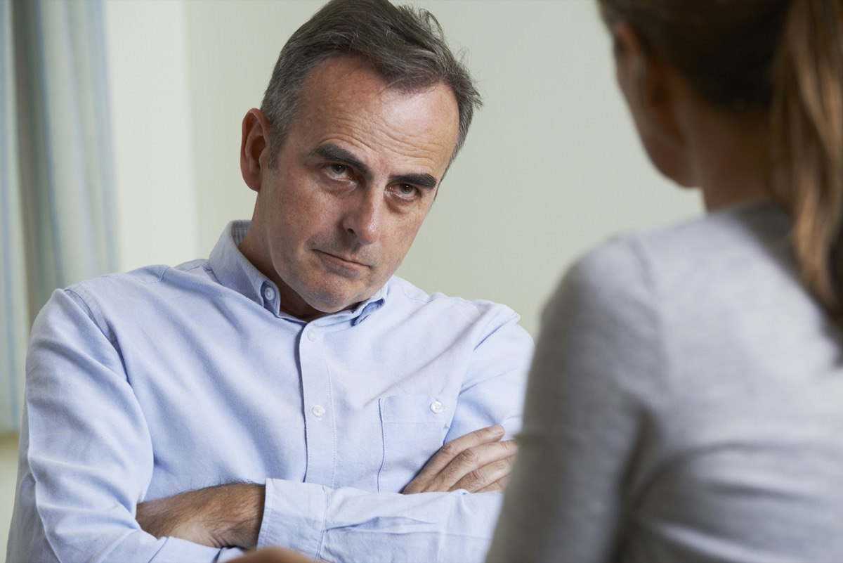 Depressed Mature Man looks angry with arms crossed