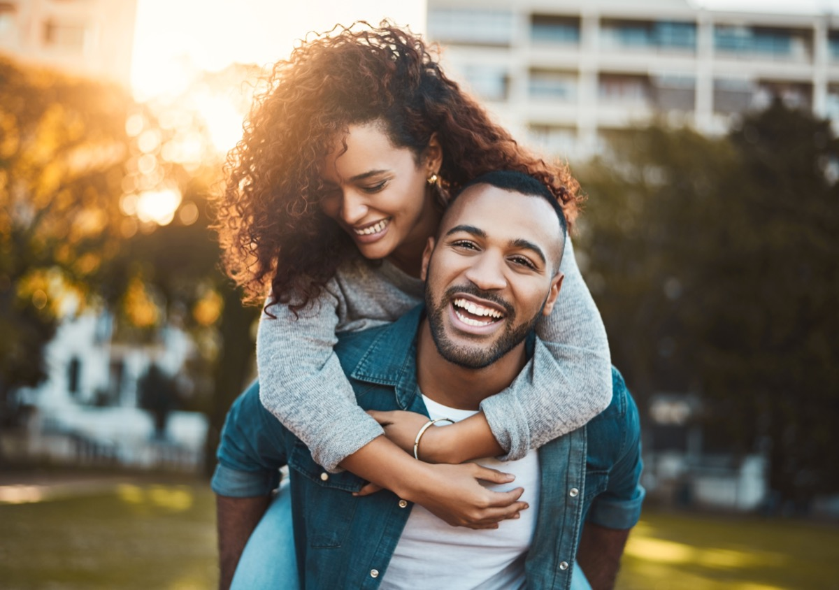smiling man giving his girlfriend a piggyback ride