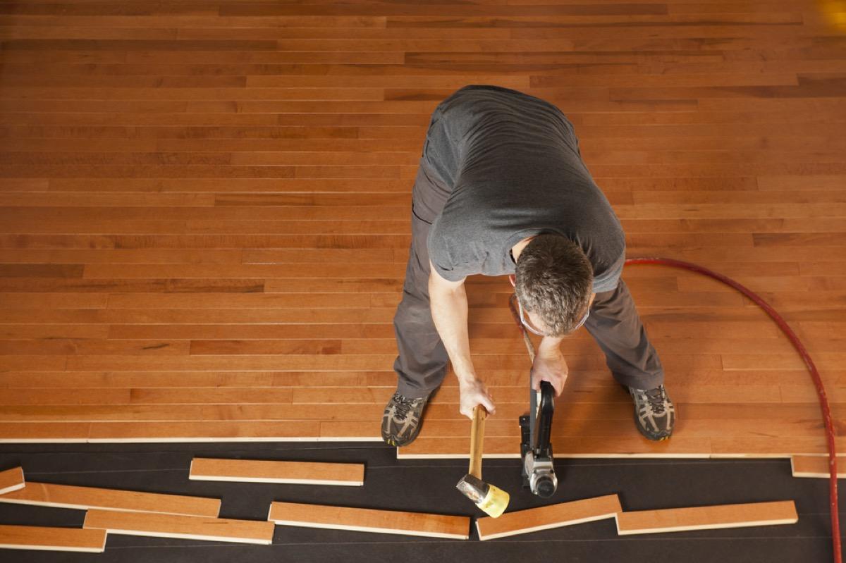 man in gray shirt and pants installing hardwood floor