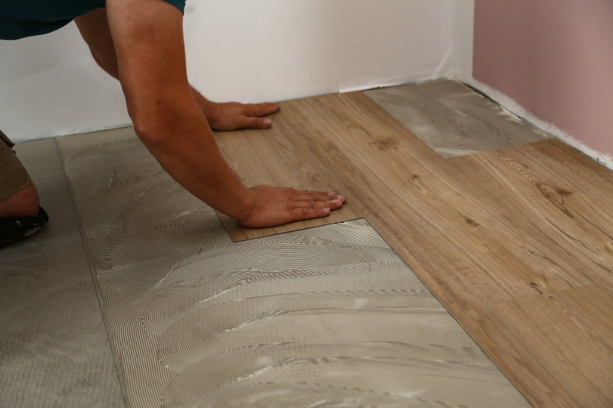 man installing wood grain tile floor