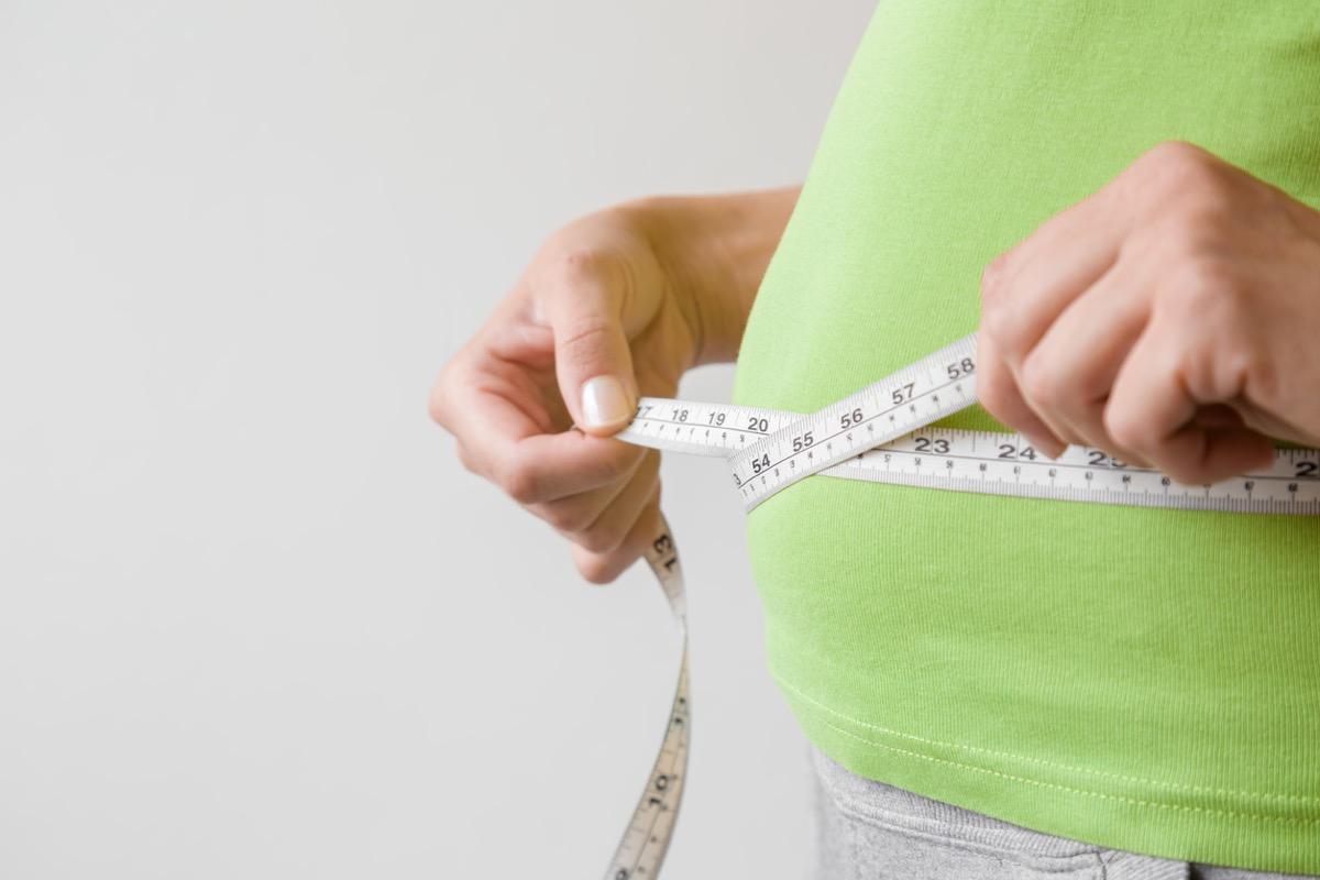 Overweight woman measuring her waist.