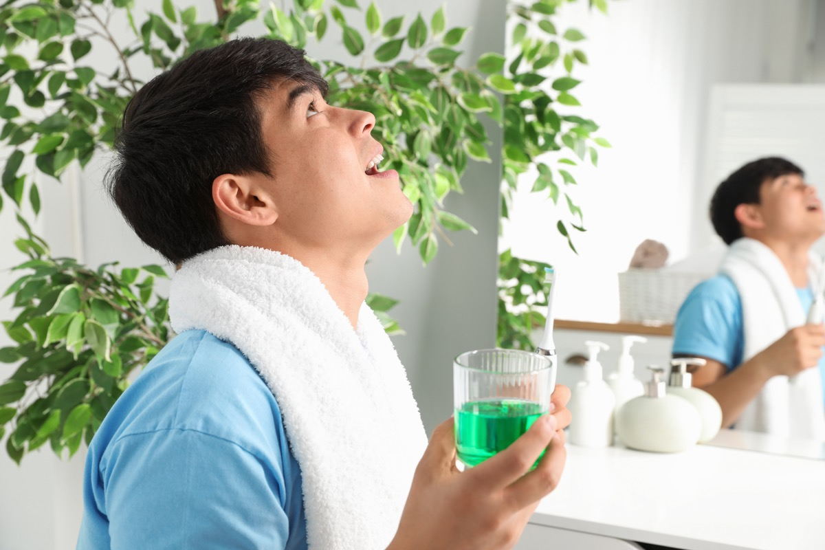 Man gargling mouthwash by his sink