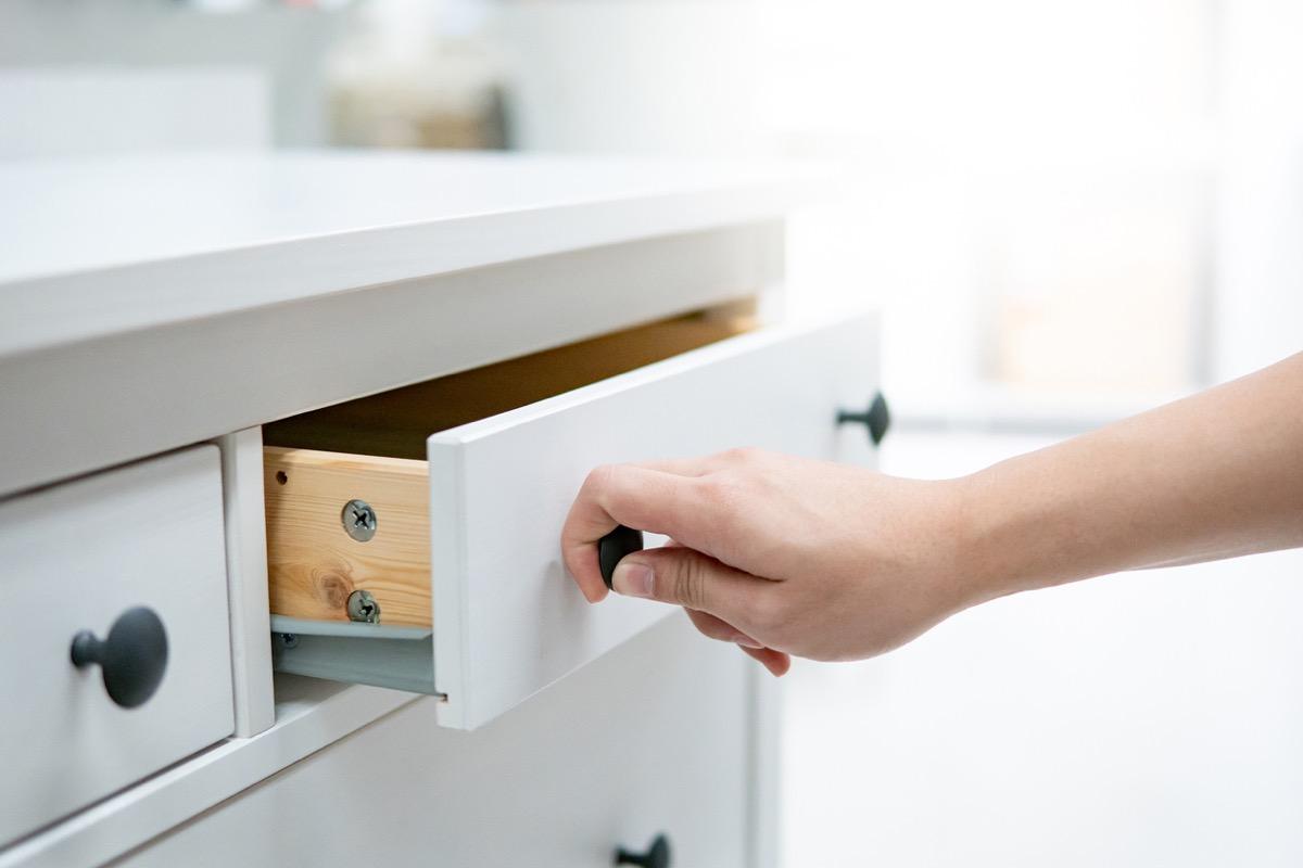 white man opening white kitchen drawer with black knob