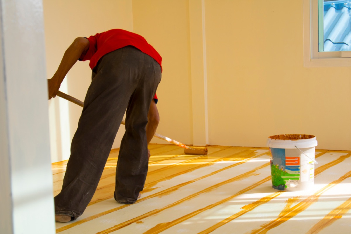 man in red shirt and black pants painting wood floors yellow