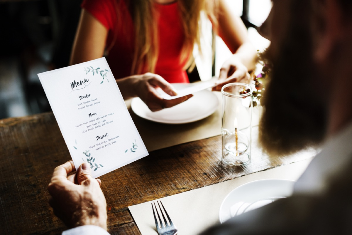 white man reading menu at dinner with woman in red dress