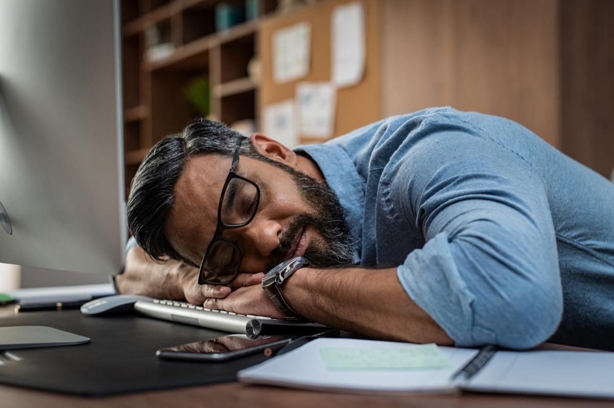 Tired multiethnic businessman sleeping in office