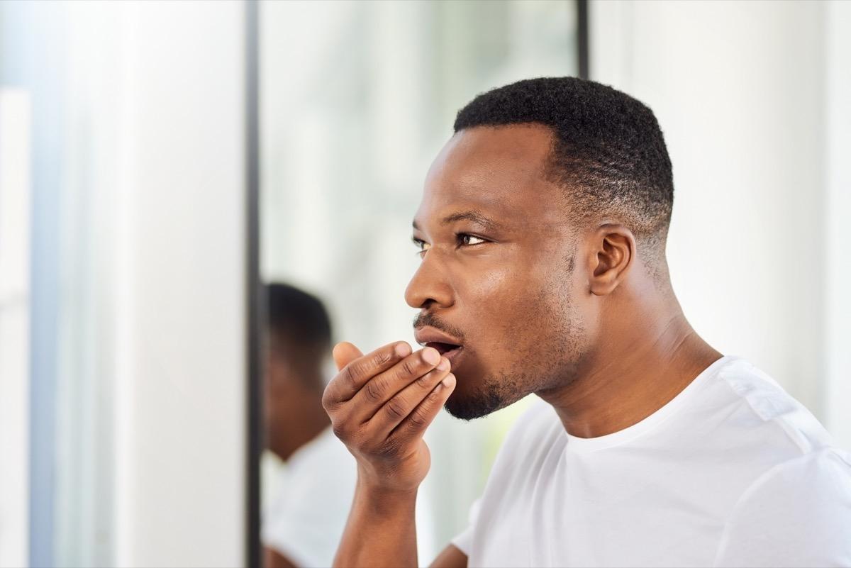 Black man smelling his breath