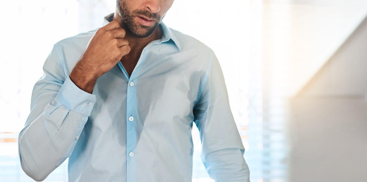 Young white man sweating through shirt