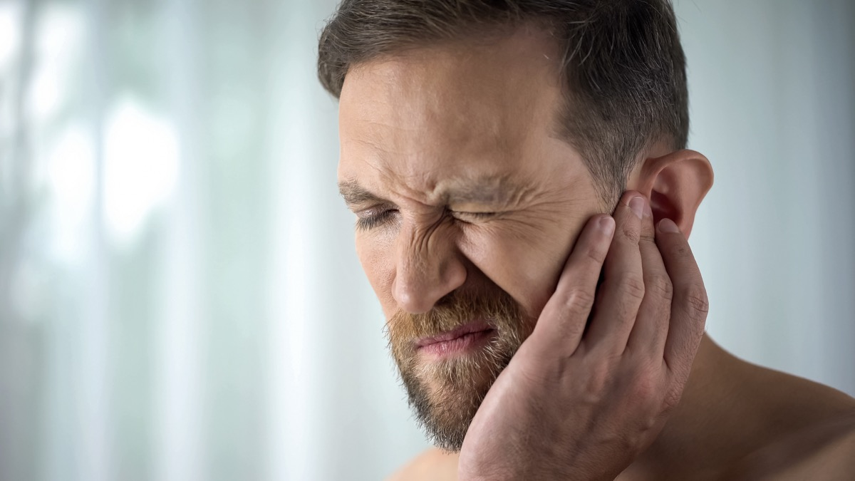 Man holding his mouth because of tooth pain
