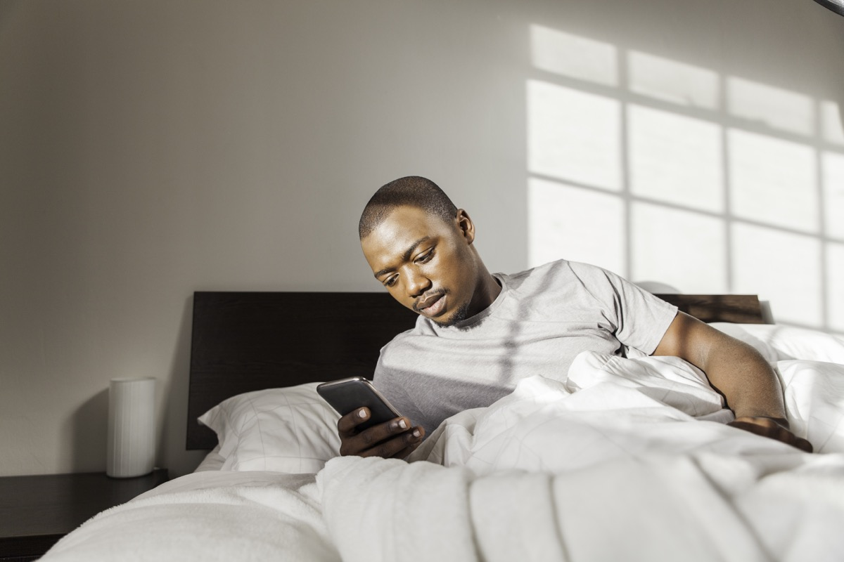 man using his phone in his bed