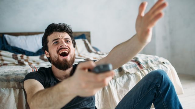 Man is angry while he is watching television on the floor