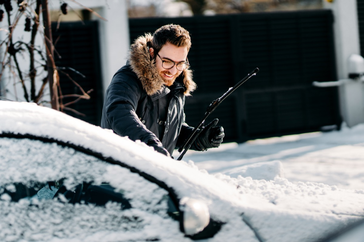 man with snow all over his car