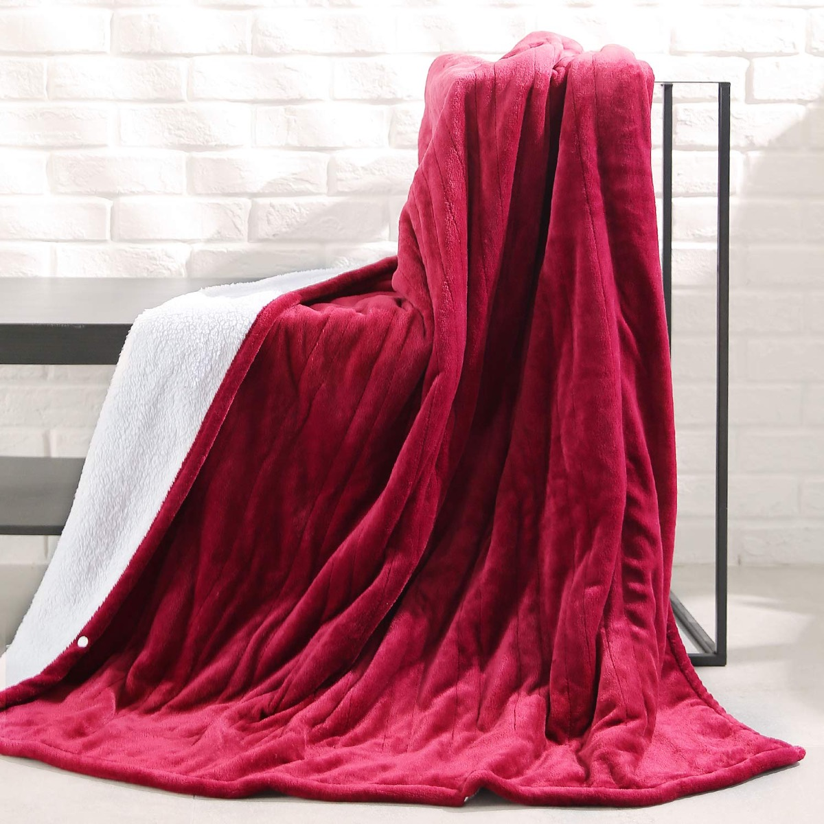 maroon blanket with white fleece lining draped over bench