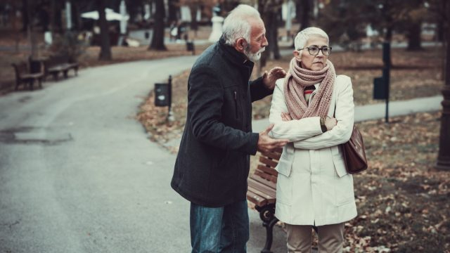 Elderly Couple in Warm Clothing Arguing in a Park During Cold Autumn Day.