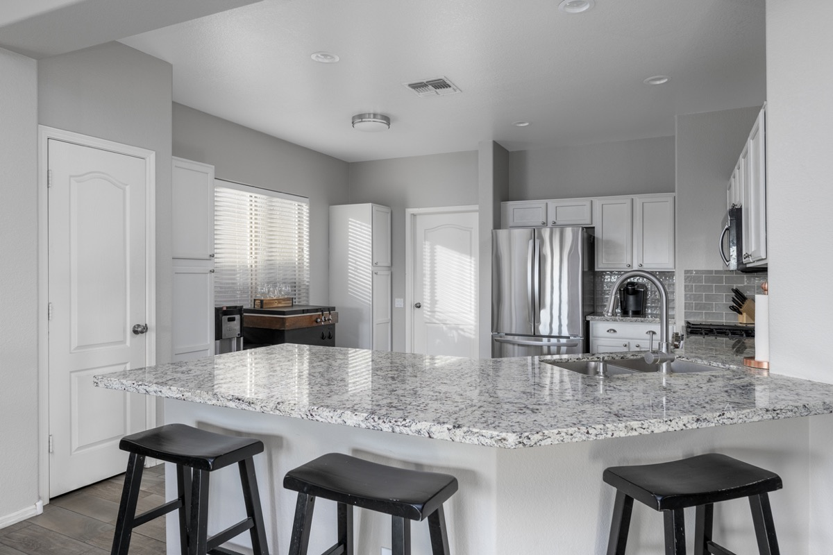 modern kitchen with granite counters and black stools