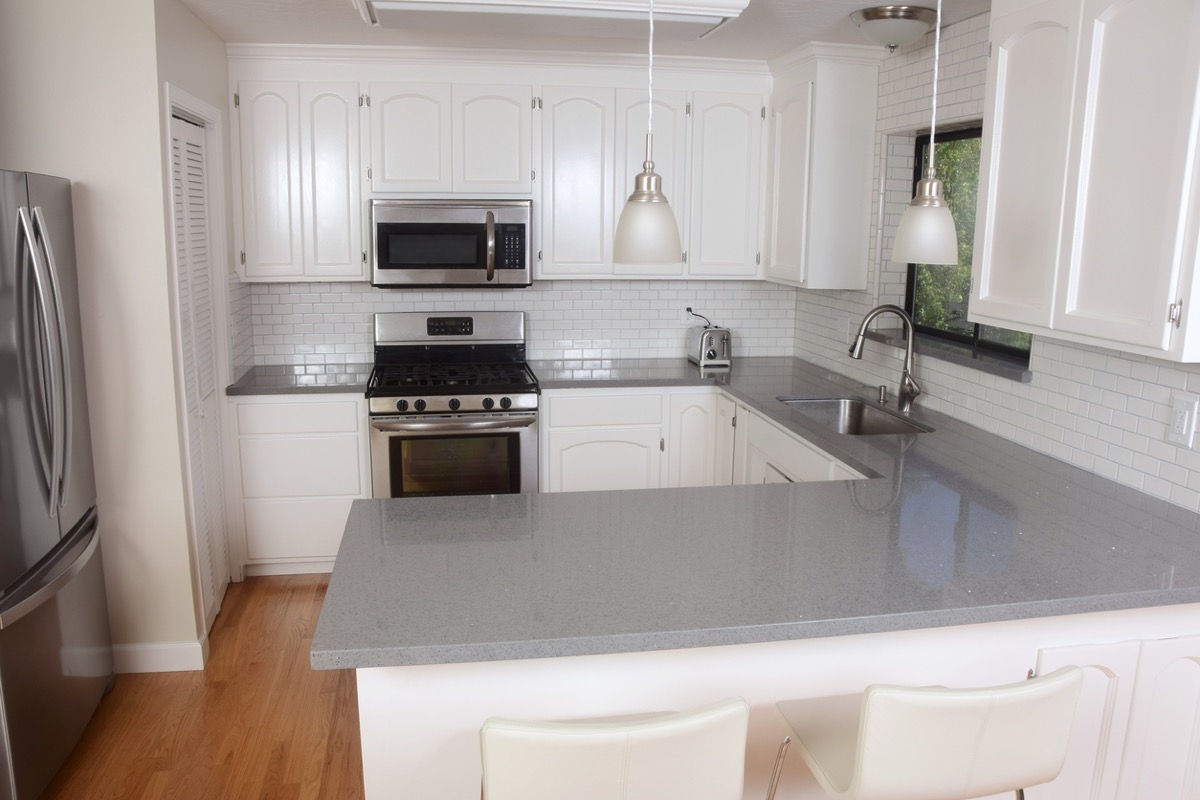 modern kitchen with gray stone counters and white cabinets and subway tile backsplash
